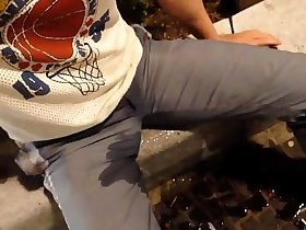 Selfpissing next to busy shopping       street